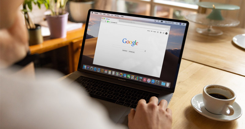 A man uses a browser window to open Google on his laptop